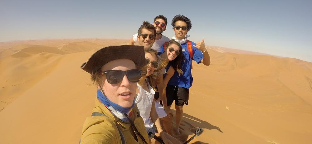 Students hiking dunes in Africa by Trevor McCord