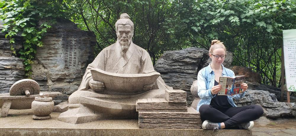 Student reading in front of statue in China by Isabelle Boes