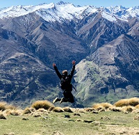 Student jumping in a field overlooking Queenstown, NZ by Sydney McDaniel