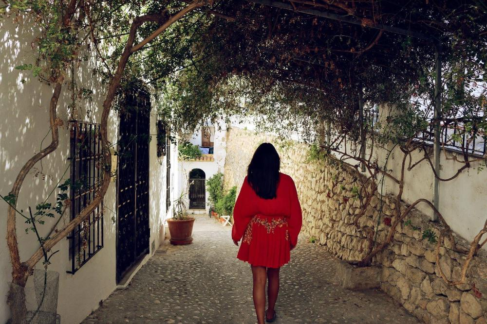 Woman walking down Spanish alley by Tessa Diestel