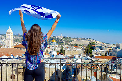 Girl overlooking Tel Aviv Holding the flag of Israel